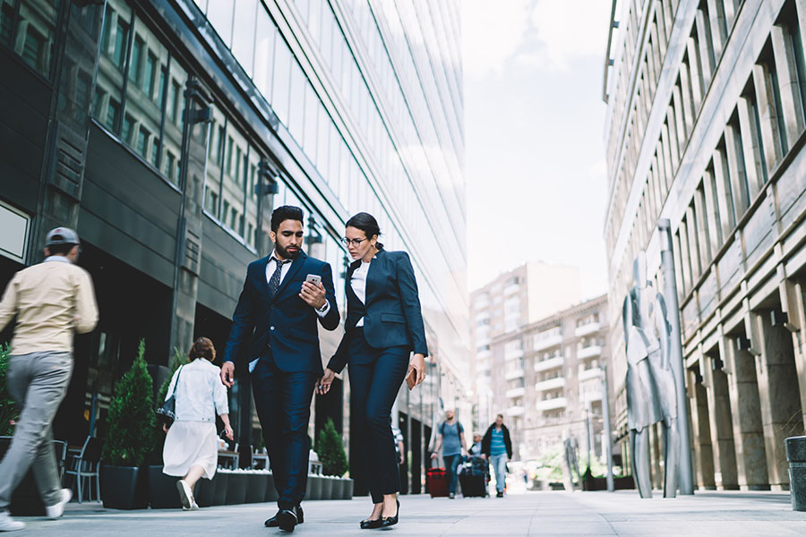 Contact - Two Business People Walking Down Street in the City Looking at a Phone